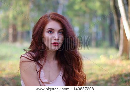 Sexy woman in jersey and with red hair poses in autumn forest shallow dof