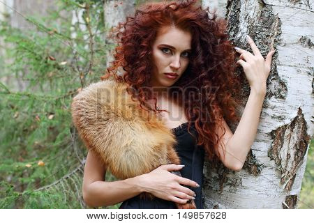 Beautiful woman in corset with fur stands near birch in forest