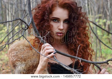 Beautiful girl with curly hair poses among tree branches in autumn forest