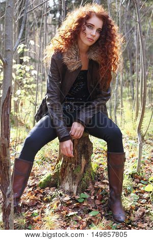 Beautiful girl in boots sitting on tree stump in sunny autumn forest