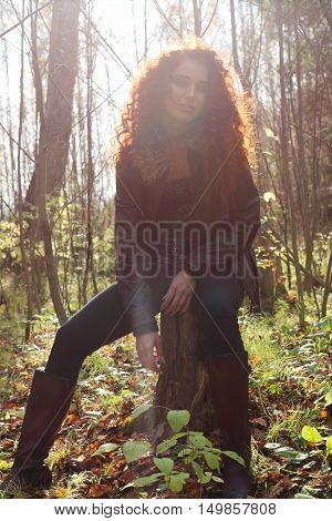 Beautiful girl in boots and jacket sitting on tree stump in sunny autumn forest