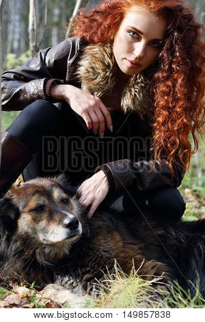 Beautiful girl in boots and jacket sits with dog in sunny autumn forest