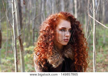 Beautiful woman with curly hair in leather jacket poses in sunny autumn forest