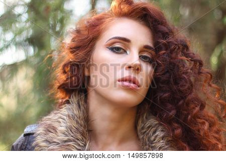 Girl with curly red hair poses in sunny autumn forest shallow dof