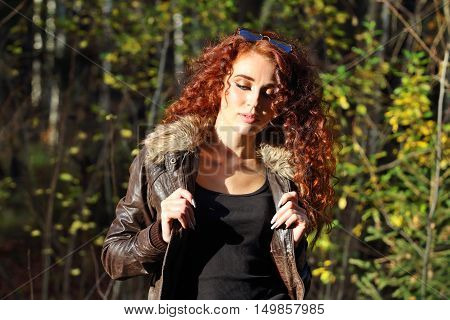 Pretty woman with sunglasses poses at sunny day in autumn forest