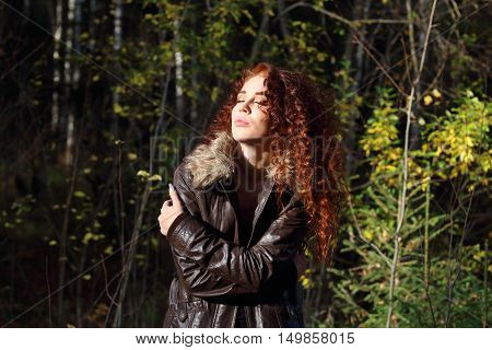 Young pretty woman in jacket with closed eyes basks in sun in forest
