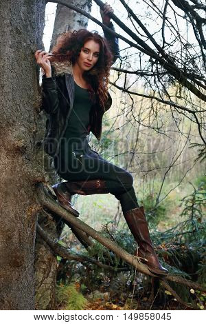 Happy woman in boots with curly hair poses on old fir-tree in forest