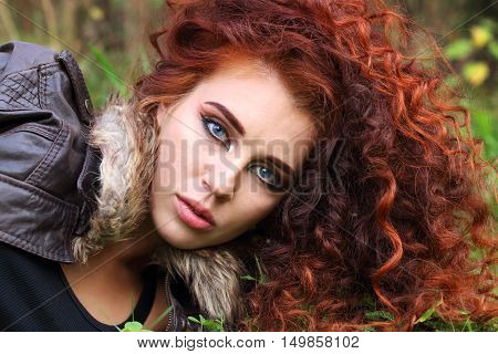 Pretty woman with curly hair in jacket on grass in field shallow dof