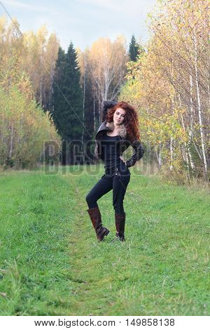 Beautiful woman in leather jacket stands on grass in autumn forest