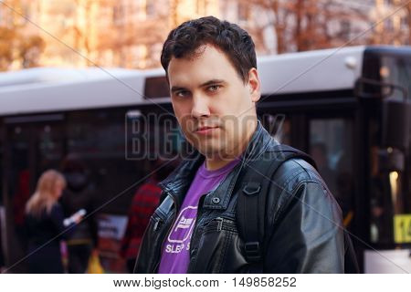 Man in leather jacket stands on street near bus stop in city shallow dof