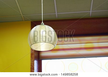 Close up view of lamp hinging from ceiling in cafe with yellow walls