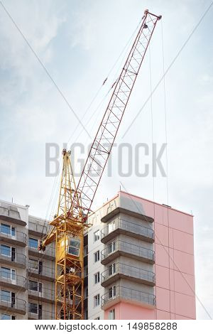 Big yellow stationary hoist and part of building under constructio sky with clouds