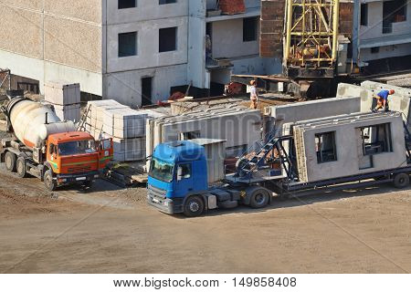 Concrete mixer truck workers on construction site with new building at autumn day