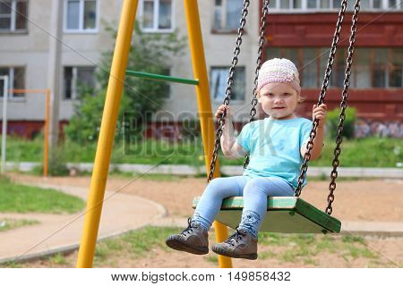 Little cute girl in hat swings on children playground at summer day