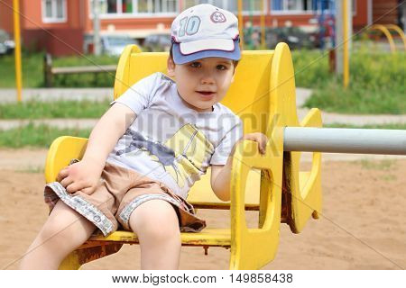 Little cute happy boy rides on carousel on playground at summer day