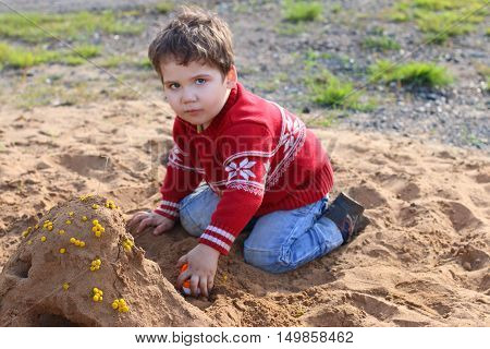 Happy handsome little boy plays with toy car in sand at summer day