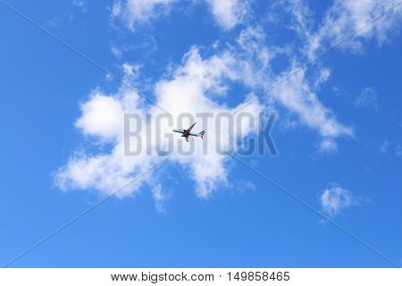 Under view of modern passenger airliner in blue sky with white clouds