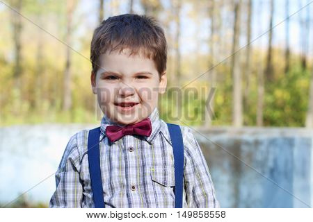 Handsome little plump boy in shirt and bow tie grimaces in sunny green park