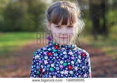 Cute little girl stands in sunny green park shallow dof close up