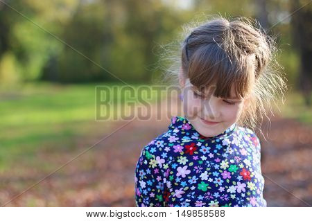 Cute little girl smiles and looks away in sunny green park shallow dof close up