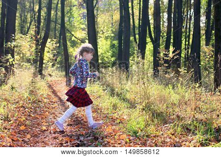 Cute little girl in red skirt runs in sunny green park with dry foliage