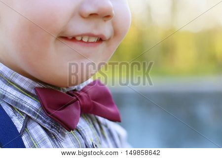 Chin and smiling mouth of little cute boy on bow tie outdoor