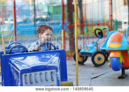 Happy cute little boy rides on car of carousel at summer day in park