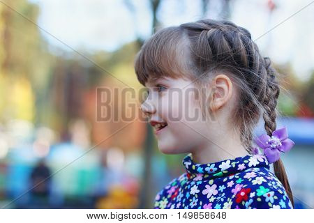 Happy little cute girl smiles and looks away outdoor shallow dof