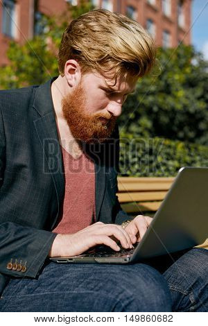 Red beared office manager hard working with computer outdoor. Stylish man in suit red t-shirt and jeans sit on bench. Calm emotion on the face.
