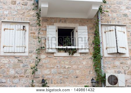 Open Window With Flowers And Two Closed Windows With White Shutters On A Stone Wall