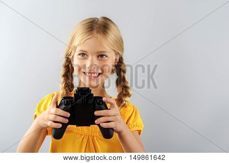 modern kids concept, girl holding gamepad isolated on grey background