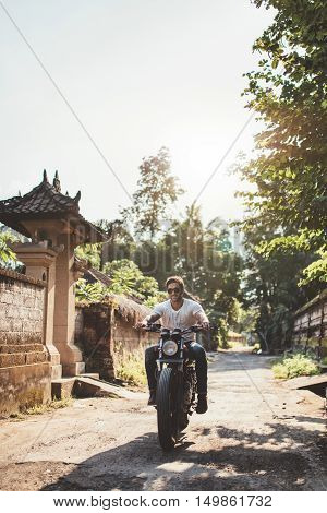 Vertical shot of young man riding motorcycle with her girlfriend through a village road. Couple out on a motorbike ride.