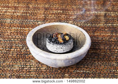 Myrrh burning on a hot coal. Myrrh is an aromatic resin, used for religious rites, incense and perfumes