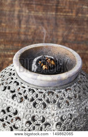 Myrrh burning on a hot coal. Myrrh is an aromatic resin, used for religious rites, incense and perfumes.
