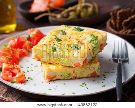 Omelet with smoked salmon and broccoli on a plate.