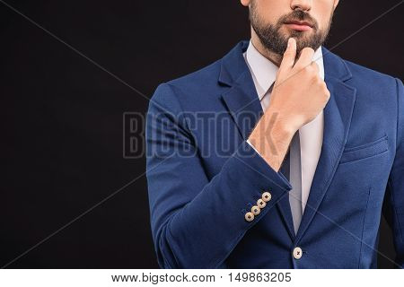 Pensive businessman is touching his beard thoughtfully. He is standing in blue suit. Isolated and copy space in left side