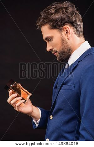 Young man is holding cologne and looking at it with satisfaction. He is standing in blue suit. Isolated on black background