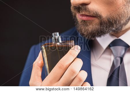Close up of bearded man is smelling cologne with pleasure. He is standing in suit. Isolated