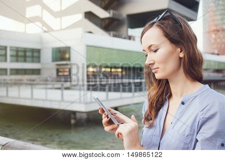 Nice woman is holding smart phone and using city map application for finding the location address. Caucasian female is standing near modern buildings and typing message. Copy-space for your advertisement text