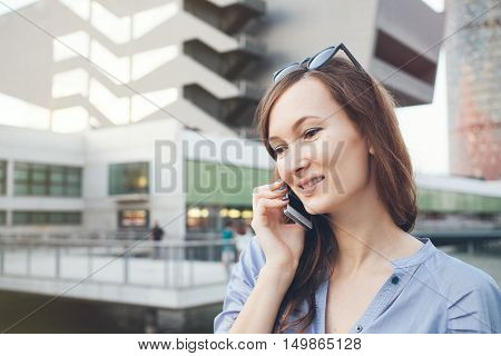 Young business lady is talking on smart-phone and smiling with her teeth. Happy telephone conversation concept. Woman is having phone conversation with clients discussing job moments