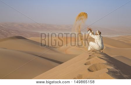 Man in traditional outfit in a desert at sunrise throwing sand