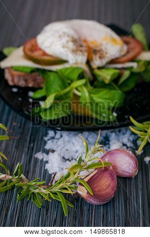 cooked Breakfast of poached eggs with greens and tomatoes on dark background