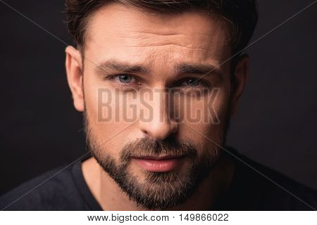 Mistrustful young man is standing and looking forward with doubt. Isolated