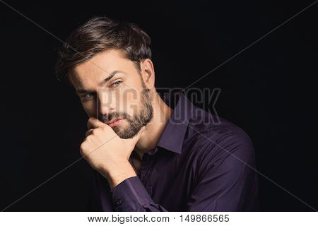 Thoughtful guy is making serious decision. He is sitting and touching his beard. Isolated on black background