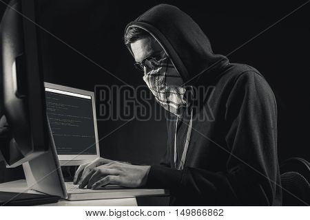Young male hacker is typing on computer with aspiration. He is sitting and wearing mask. Black-and-white