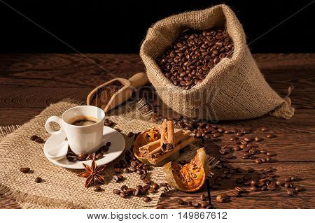 Coffee cup with cinnamon star anise dried orange fruit and coffee sack over a wooden background