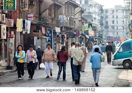 Shanghai, China - October 23, 2006: People go to the grocery store in a suburban street with typical houses and shops.