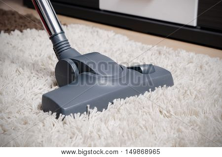 Vacuum Cleaner Cleans The White Shaggy Carpet.