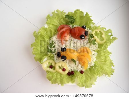 Fishes are made of tomatoes. Ridiculous food for good mood. The dish consists of tomatoes, olives, rice, salad, parsley