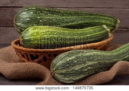 green zucchini or courgettes on sackcloth wooden background.